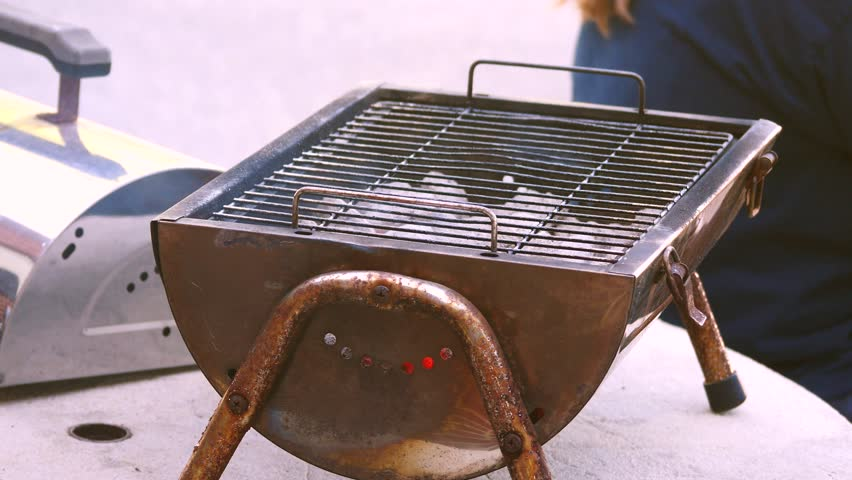 Portable Tabletop Charcoal Grill With Instances Of Fire Visible Through Tiny Holes A Person S Back In Background