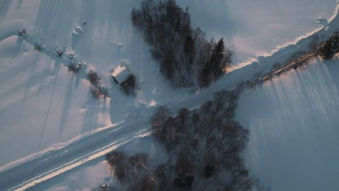 Aerial flight over Swedens snow covered countryside, revealing beautiful sunset in 4k.