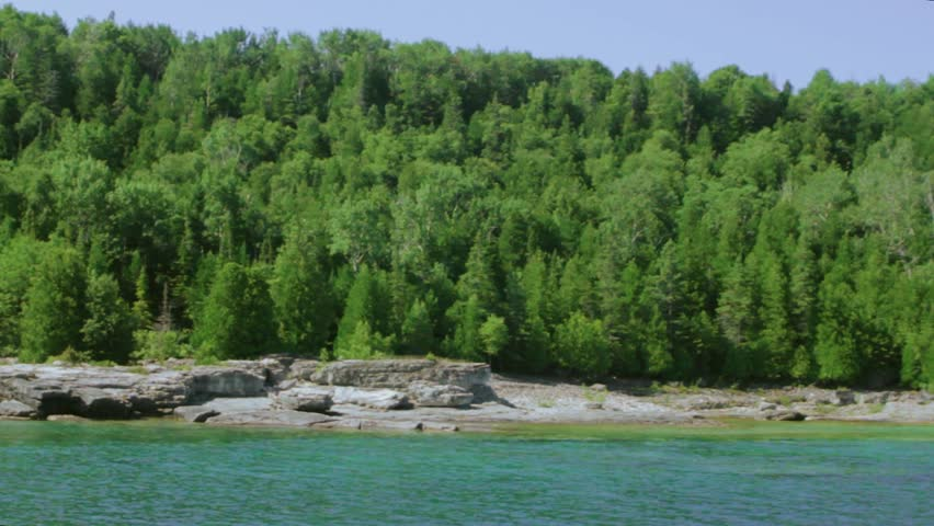 View from boat passing forest on Flowerpot Island, Bruce Peninsula, Ontario, blue water, landscape