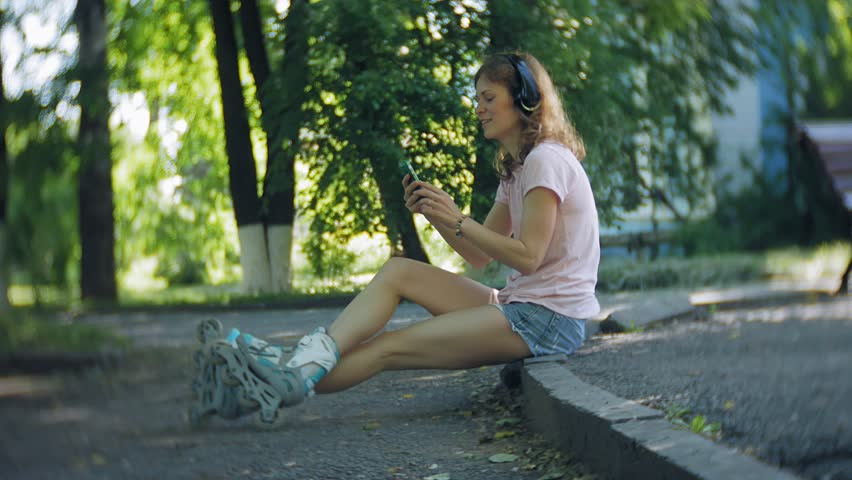 woman rollerblading and listening to music on headphones on the phone in the park 4k #1013402990