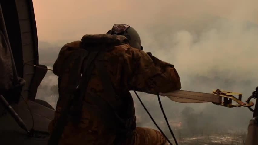 CIRCA 2017 - A member of the California National Guard rides in a helicopter surveying the Thomas Fire in Ventura.