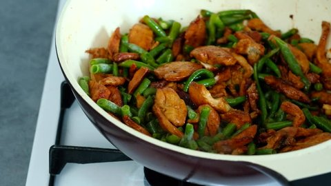 Chef stirring green beans with chicken meat and soy sauce in wok. Stewed vegetables with chicken. Chinese food preparation at home