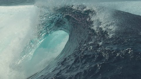 SLOW MOTION, CLOSE UP: Big splashing barrel wave rushes towards the coast of an exotic island in the sunny Pacific. Glassy droplets of water shine in the summer sun as big tube wave crashes wildly.