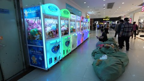 GUANGZHOU, CHINA - MARCH 14, 2018: Many claw crane machines stay in row at passage, sa?ks full with plush toys lie against. Unidentified man sit and wait to do maintenance of gaming automates