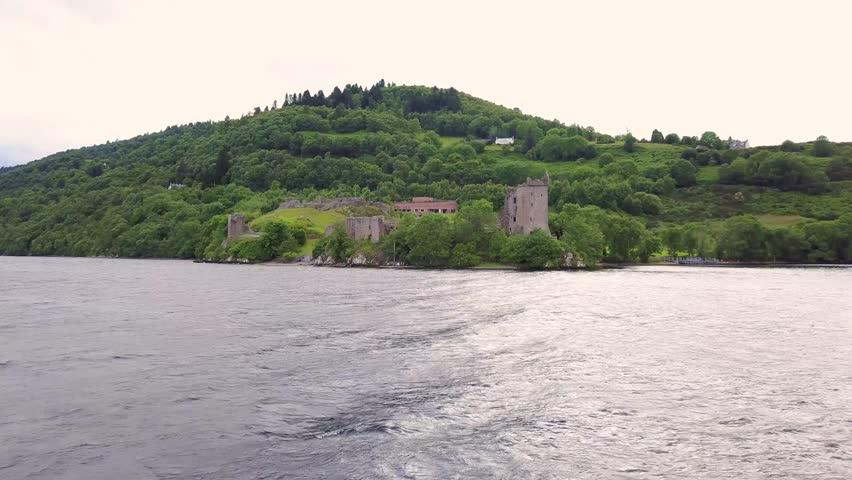 Loch Ness - low altitude over water with speedboat racing across - towards Urquhart Castle