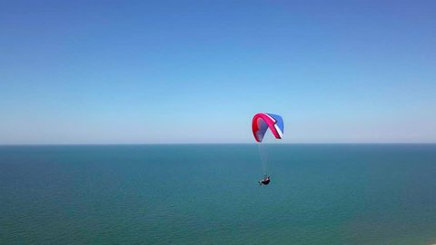 Aerial View. The paraglider flies over the coastline. The wing of the paraglider is blown by the wind. Row of sea and forest
