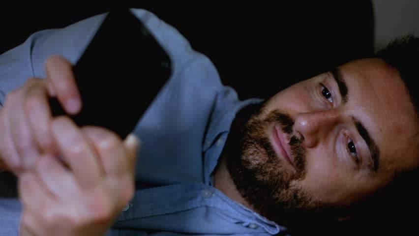 The video is about one happy man using smartphone at night and chatting.The shot is fixed on the man. | Shutterstock HD Video #1013486360