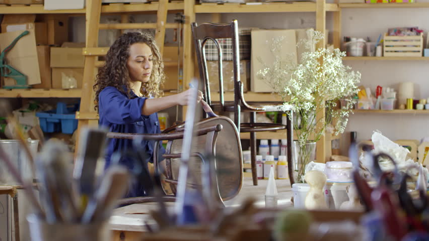 Pretty young woman with curly hair using brush to apply varnish on old wooden chairs in carpentry workshop | Shutterstock HD Video #1013491670