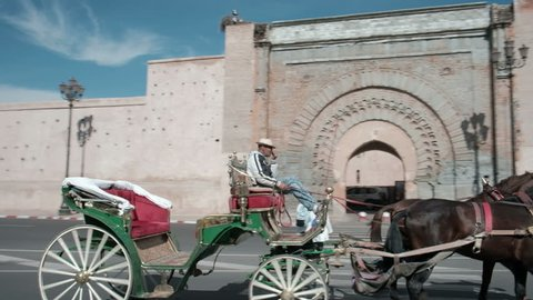 Marrakech, Morocco - March 26, 2018: Sweeping camera pan right following caleche horse carriage to reveal panoramic view of ancient Bab Agnaou city gate