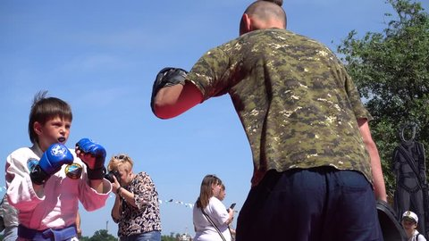 Kherson, Ukraine - 26th of May 2018: 4K Katran fighting club performs at the KhersOn Festival - Boxing session of a child with Master of Jiu-jitsu outdoors