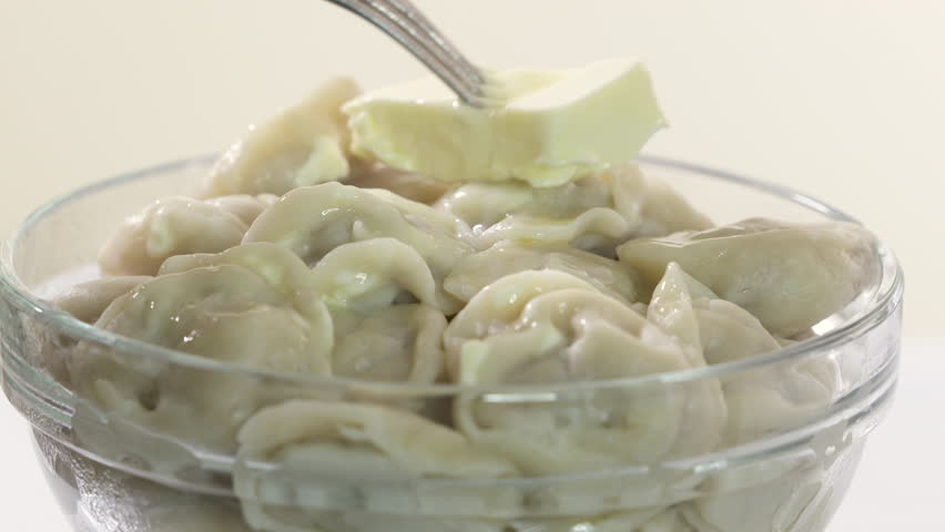 Bowl of homemade boiled dumplings with butter. Traditional Russian dish pelmeni filled with meat.