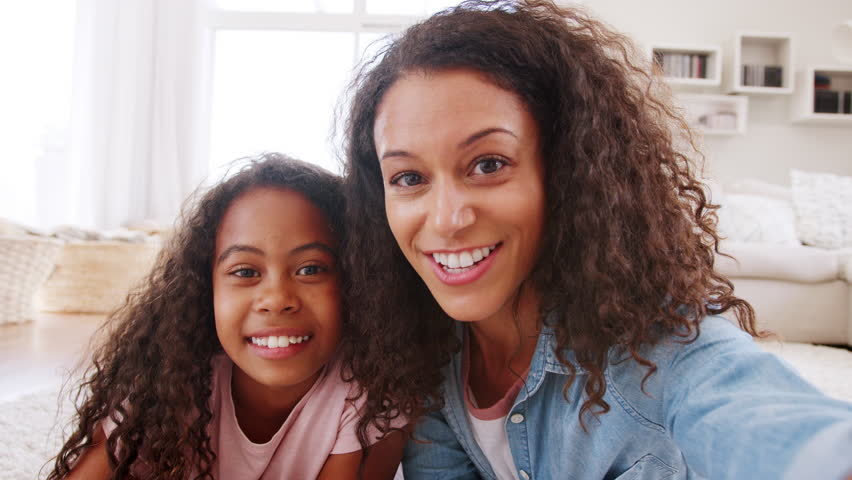 Mother And Daughter Lying On Rug And Posing For Selfie At Home | Shutterstock HD Video #1013516150