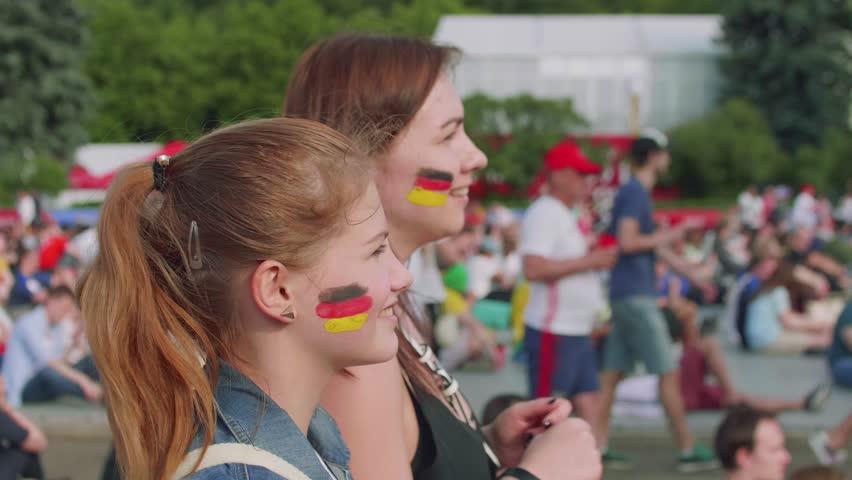 Girls cheer for German team during football match in fan zone   Shutterstock HD Video #1013519900