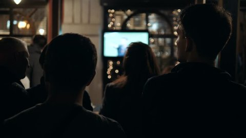 Friends watches football on TV in a sport bar silhouette in dark
