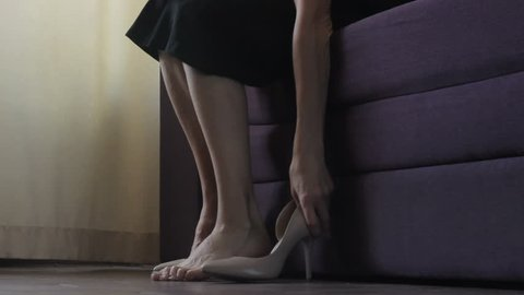 Attractive woman sitting at home, choosing, trying on modern high heeled shoes