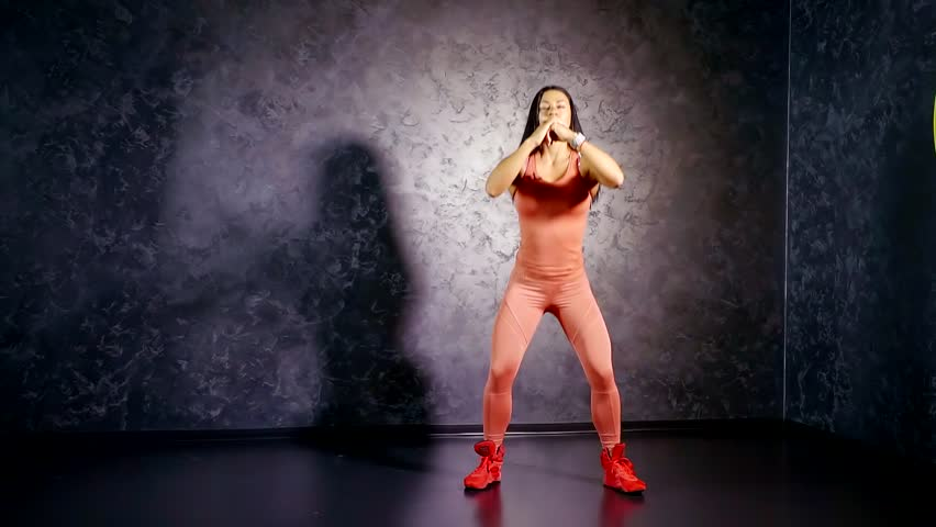 Young girl coach in a sports jumpsuit shows deep squat exercise with a rise on her toes. leg muscle training | Shutterstock HD Video #1013574560