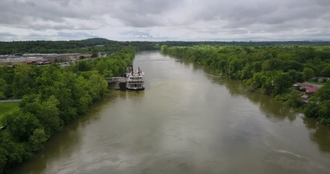 Aerial footage of a riverboat docked on the bank of the muddy Cumberland river in Nashville, Tennessee.