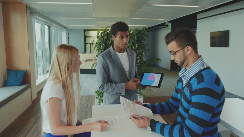 Multiracial men and woman working on report. Group of diverse woman and men with tablet in modern office hall having work with documents and statistics. | Shutterstock HD Video #1013575670