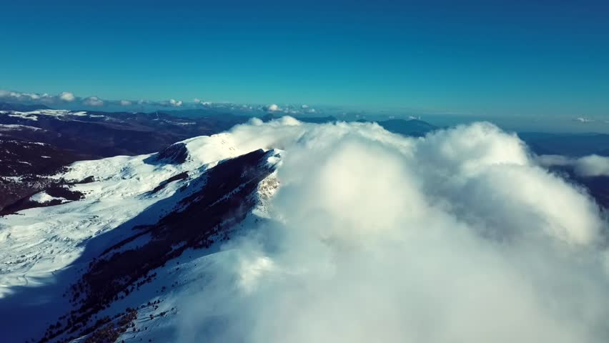 Aerial drone footage of snowy mountain above clouds #1013583860