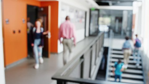 Defocused Shot Of Busy High School Corridor During Recess With Students And Staff