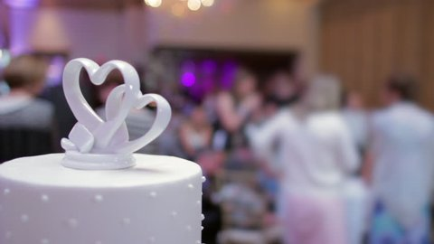 Wedding Cake Hearts topper foreground blurry hall background