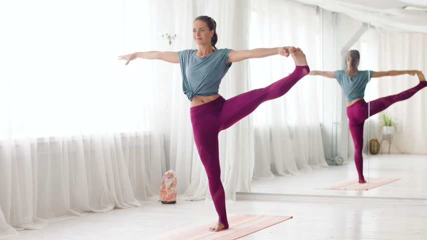 fitness, people and healthy lifestyle concept - young woman doing yoga extended hand-to-big-toe pose at studio