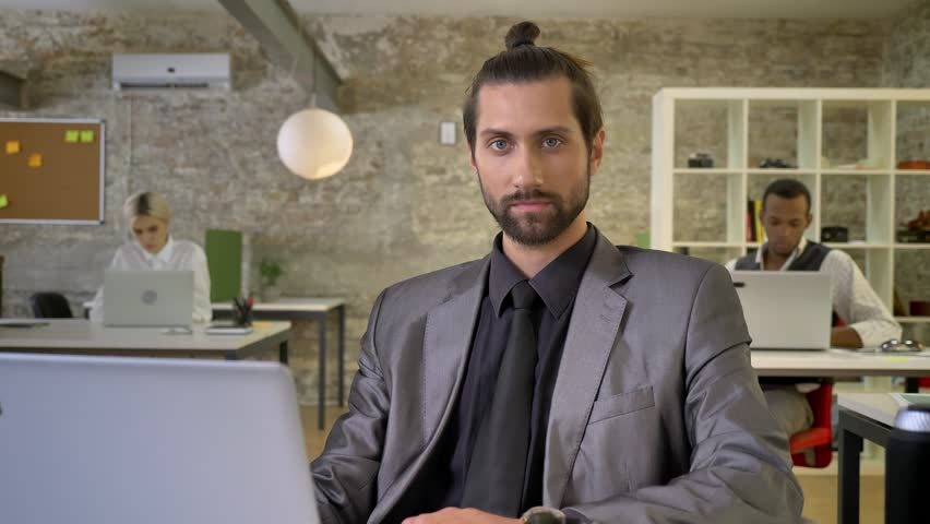 Confident businesswoman with beard is sitting at laptop in office, watching at camera, colleagues are networking with technologies, work concept, communication concept. | Shutterstock HD Video #1013617130