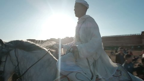 Meknes, Morocco - March 31, 2018: Pan left Moroccan competitor on horseback with traditional rifle leaving the field after competing in Tbourida or Fantasia competition