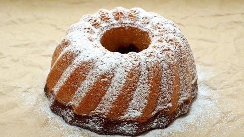 Slicing the cake. Traditional homemade marble cake. Sliced marble bundt cake on paper. 4k resolution.