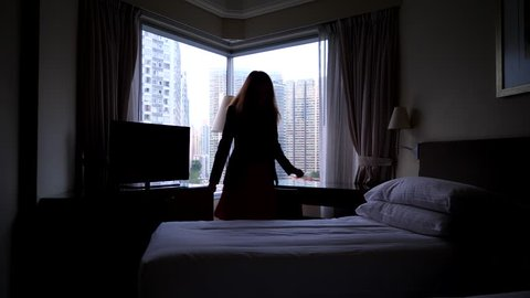 Woman feel sick, come and lay down on bed in suit and skirt, dark bedroom, bright city buildings seen outdoors through window glass. Long haired lady become unwell or sad, rest alone at dim room