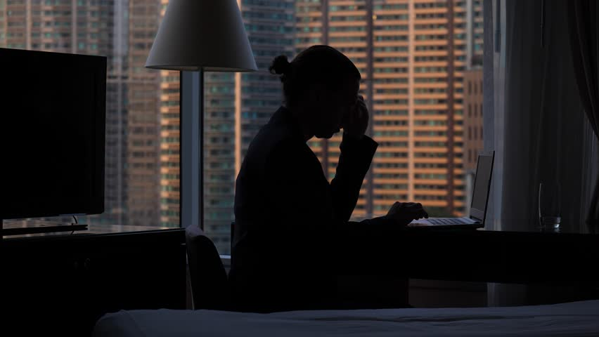 Remote worker sit at laptop against window, black silhouette of man wearing casual jacket. Blurred city mansion seen outdoors, evening time. Man lean head to one hand, put finger on computer touch   Shutterstock HD Video #1013665010