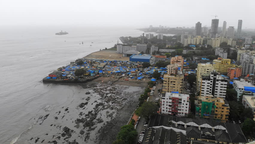 Aerial panoramic view of cityscape of Mumbai (Bombay) during monsoon season, poor slum in foreground, business district skyscrapers skyline in background - capital city of Maharashtra, India, Asia