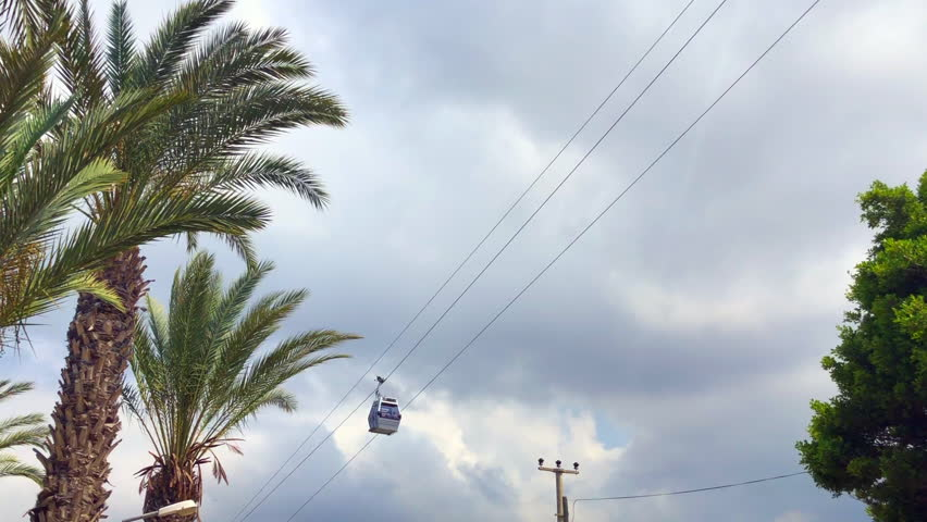 Ropeway cabin on the background of palms and clouds
