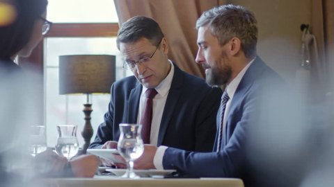 Tracking shot of business people using tablet computer when discussing potential partnership at meeting in restaurant or cafe