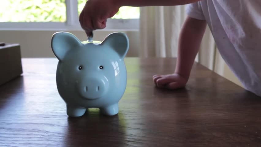 Close up footage of a youg childs hand putting money into a blue piggy bank   Shutterstock HD Video #1013704730