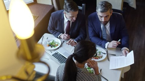 High angle view of three colleagues discussing contract when sitting at table in cafe or restaurant and having business lunch