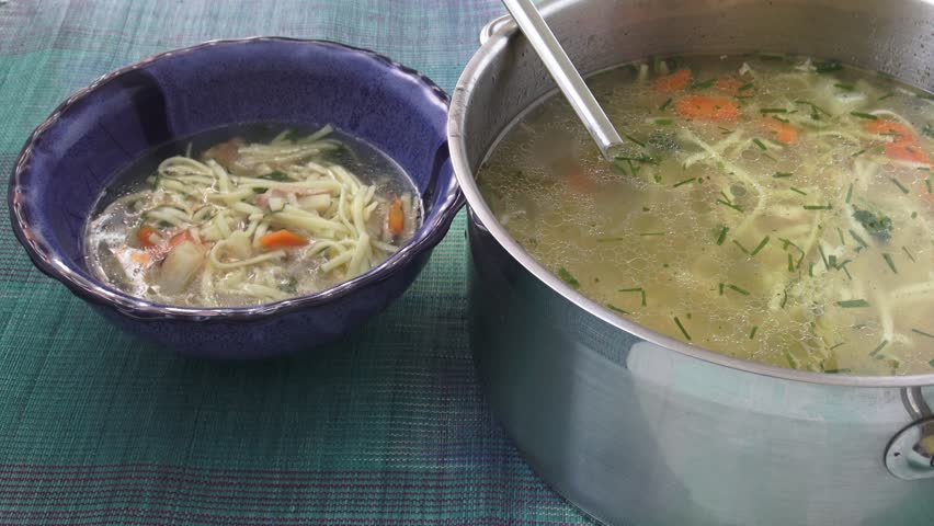 Chicken noodle soup - broth. Traditional chicken soup served in a bowl.