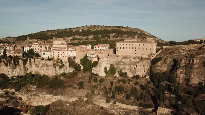 "Aerial view of Cuenca, an ancient Spanish town built on a cliff edge. Drone flies over a canyon and the ""hanging houses"" (casas colgadas) surrounding it"