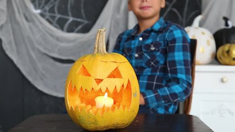 Closeup portrait of cute funny smiling kid with orange pumpkin at Halloween celebration. Boy posing for photo happily, looks at camera. Real time full hd video footage.