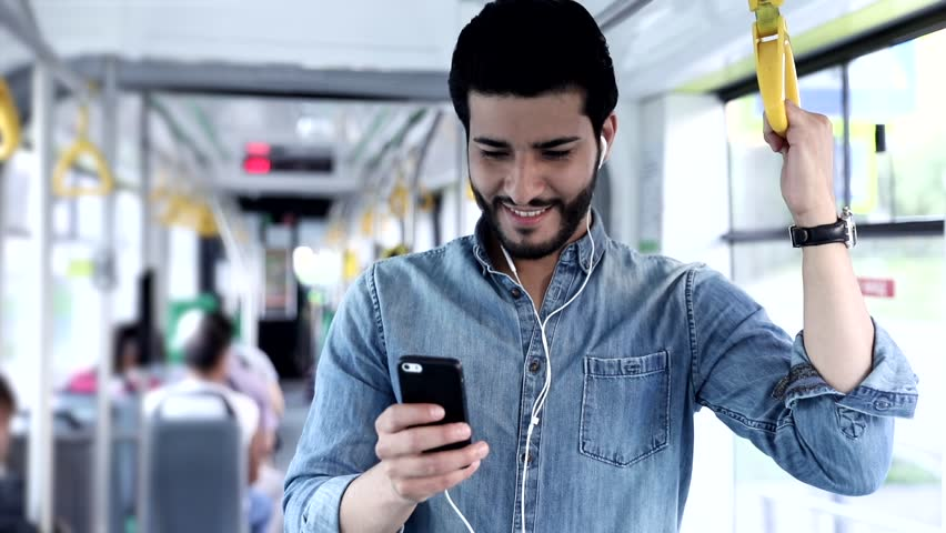 Close up view of Handsome Man Standing on the Public Transport. Interior of Crowded Tram. Man Types on his Mobile Phone. Listening to Music with his Headphones. Luxurious Wristwatch. Casual Clothing. | Shutterstock HD Video #1013754590
