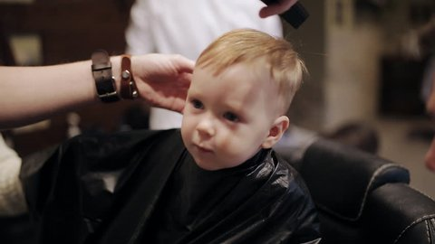 Baby first hair cut time in a hairdressing salon