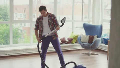 Cheerful man is engaged in cleaning and imagines that he plays the guitar
