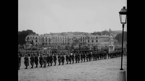 CIRCA 1919 - Soldiers march and cars drive up to the Palace of Versailles for the Paris Peace Conference.