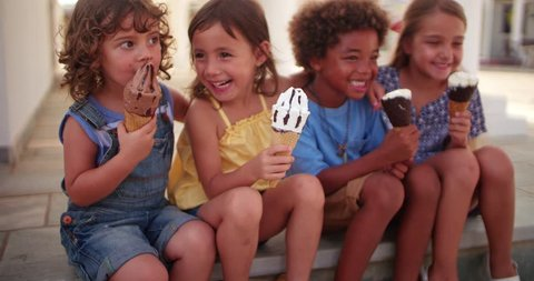 Multi-ethnic young best friends kids eating ice-cream together on summer holidays sitting on step outdoors
