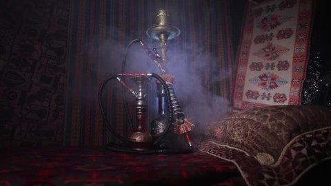 Hookah hot coals on shisha bowl making clouds of steam at Arabian interior. Oriental ornament on the carpet. Stylish oriental shisha in dark with backlight. Slider shot. Empty space