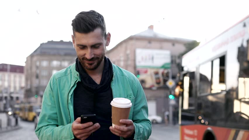 Attractive Young Man Walking Down the Street in Big Town. Holding Tasty Coffee, Mobile Phone. Chatting in Social Networks. Casually Dressed. Cars, Buses, Trams on the Background. | Shutterstock HD Video #1013876840