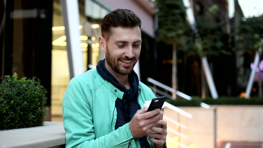 Handsome Man Standing near the Office Building's Stairs. Young Man Using his Mobile Phone. Chatting in Social Networks. Modern Building. Big City. Casual Outfit. Evening Walk. | Shutterstock HD Video #1013876870