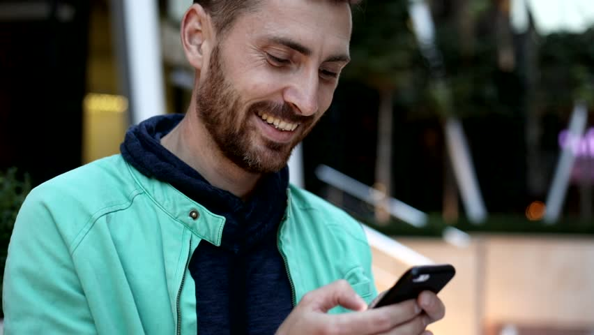 Close up view of Handsome Bearded Young Man. Typing a Message on his Mobile Phone. Chatting on it. Pleasant Mood. Casually Dressed. Enjoying his Time. Slow Motion. | Shutterstock HD Video #1013876900