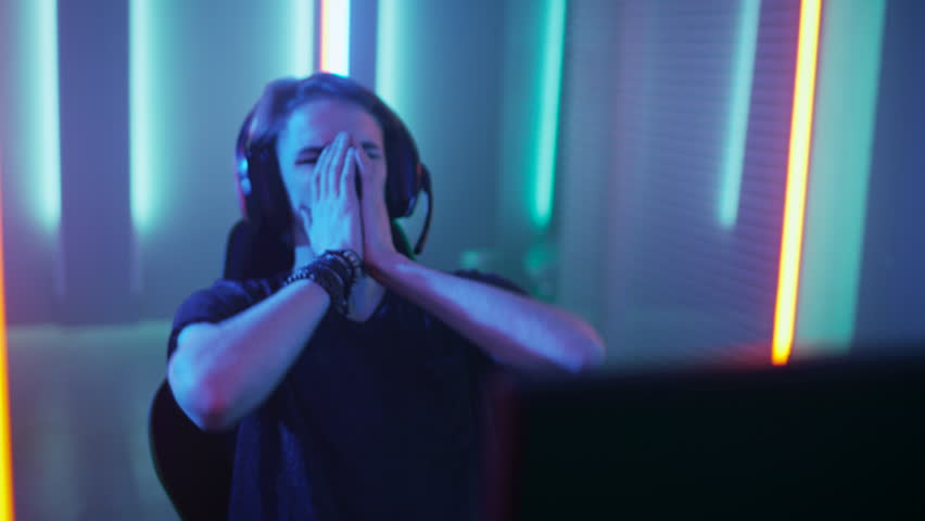 Young Pro Gamer Playing in Online Video Game Loses Big Tournament and is Disappointed. eSport Cyber Games Internet Event. Shot on RED EPIC-W 8K Helium Cinema Camera.