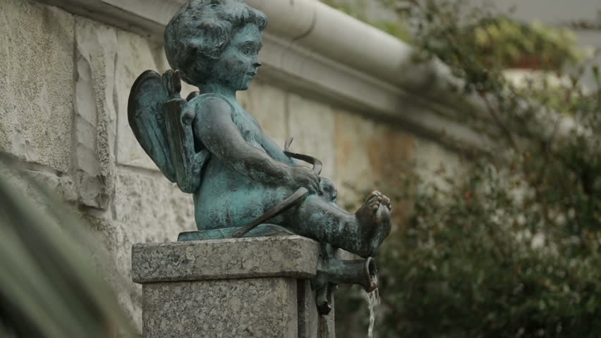 Cupid boy fountain pouring water, old town architecture in Batumi, love symbol